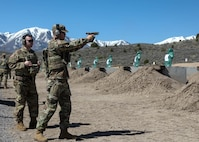 Soldier shooting pistol at range.