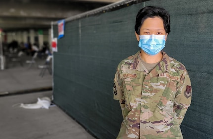 U.S. Air Force Airman 1st Class Piyaporn Rakpongs, a fleet management and analysis specialist with the 147th Combat Communications Squadron, California National Guard, monitors the walk-up site at the community vaccination center at California State University Los Angeles, March 8, 2021. Rakpongs grew up in Thailand before joining the Cal Guard.