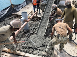 NMCB-4 places concrete for a mooring bollard at Tinian Harbor.
