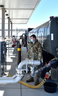 SELFRIDGE AIR NATIONAL GUARD BASE, Mich.-- Senior Airman Nick Bousquette, fuels distribution operator, 127th Fuels Management Flight based here, communicates via hand signals to a fellow fuels distribution operator while refueling an active duty C-5 Galaxy here on March 6, 2021.