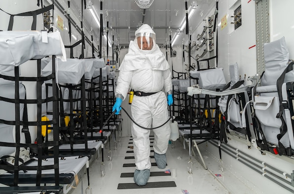 Master Sgt. Leonardo Erazo, 5th Health Care Operations Squadron medical logistics flight chief, simulates decontaminating the inside of a Negatively Pressurized Conex loaded on a C-17 Globemaster III on Dover Air Force Base, Delaware, April 7, 2021. Erazo is a member of the 775th Expeditionary Aeromedical Evacuation Flight, which conducted NPC training to include decontamination procedures of the entire NPC. (U.S. Air Force photo by Roland Balik)