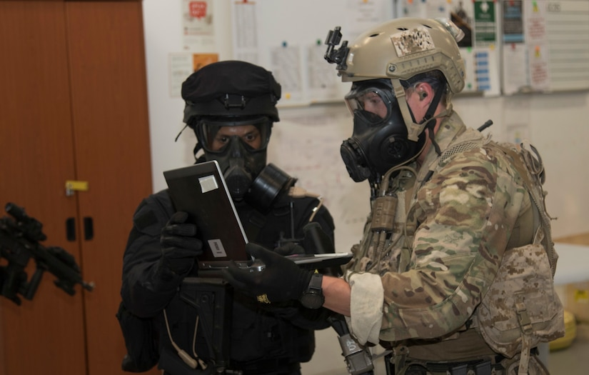A U.S. Special Operations Forces members and a Qatari Special Forces soldier obtain a computer used in the creation of a crisis scenario during exercise Invincible Sentry, March 23, 2021, near Doha, Qatar. U.S. Central Command's annual bilateral exercise enables the U.S. and Qatar to work together toward prevailing against complex regional security challenges. (U.S. Army photo by Staff Sgt. Daryl Bradford, Task Force Spartan Public Affairs)