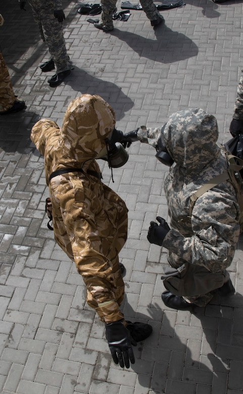 U.S. Army Soldiers from 318th Chemical Company, 1st Battalion, 35th Armored Regiment, 2nd Brigade, 1st Armored Division, Task Force Spartan, decontaminate a Qatari soldier in a simulated crisis scenario during Invincible Sentry, March 23, 2021, near Doha, Qatar. U.S. Central Command's annual bilateral exercise allows the U.S. and Qatar to work together toward prevailing against complex regional security challenges. (U.S. Army photo by Staff Sgt. Daryl Bradford, Task Force Spartan Public Affairs)
