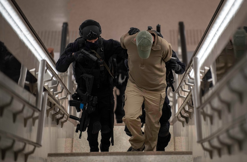 Qatari Special Forces escort a restrained gunman role-player, March 24, 2021, during U.S. Central Command's crisis response exercise Invincible Sentry in Doha, Qatar. The annual bilateral exercise represents a unique opportunity to train with Qatari partners to practice critical crisis response capabilities. (U.S. Navy photo by Mass Communication Specialist 2nd Class Alex L. Smedegard)