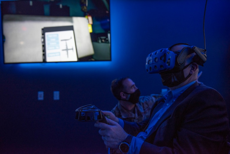 Staff Sgt. Christopher Clinton, 317th Maintenance Group Virtual Reality NCO in charge, directs Acting Secretary of the Air Force John Roth during a C-130J Super Hercules maintenance virtual reality presentation at Dyess Air Force Base, Texas, April 6, 2021. Clinton briefed Roth on the 317th MXG VR lab capabilities and advantages. Training on VR simultaneously provides Airmen with an individualized, hands-on training experience. (U.S. Air Force photo by Airman 1st Class Colin Hollowell)