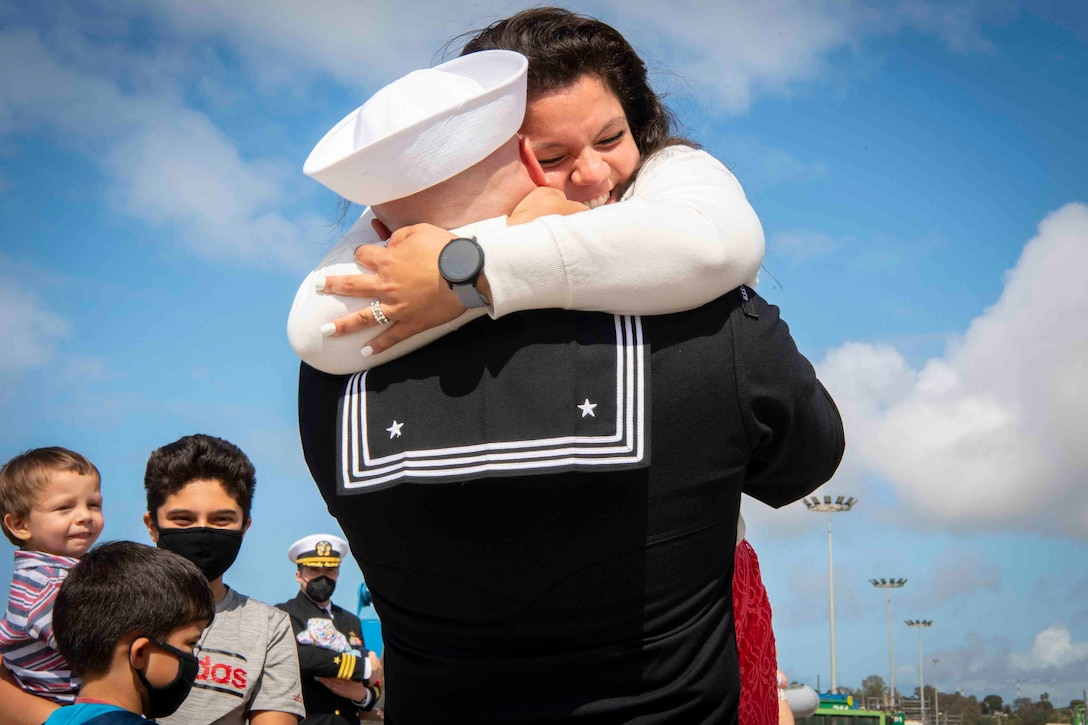 A sailor hugs a woman as three children stand beside them.