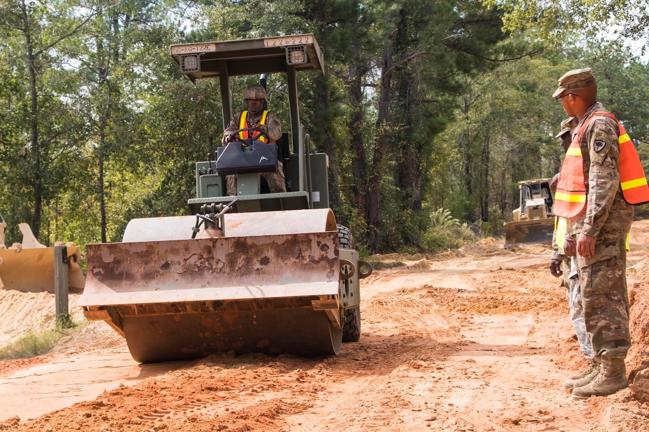 A man in a uniform operates a rolling compactor as it travels down a dirt road. Two other men in uniform stand to the side of the road.