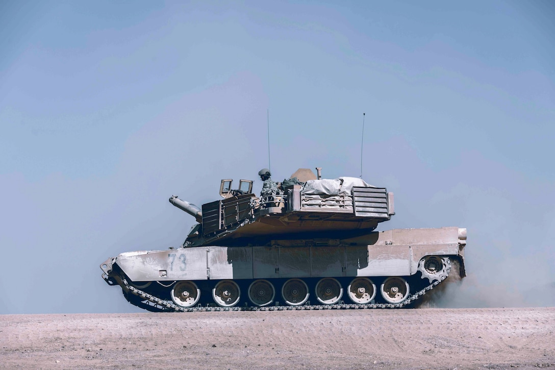 An Army tank moves over a dirt road.
