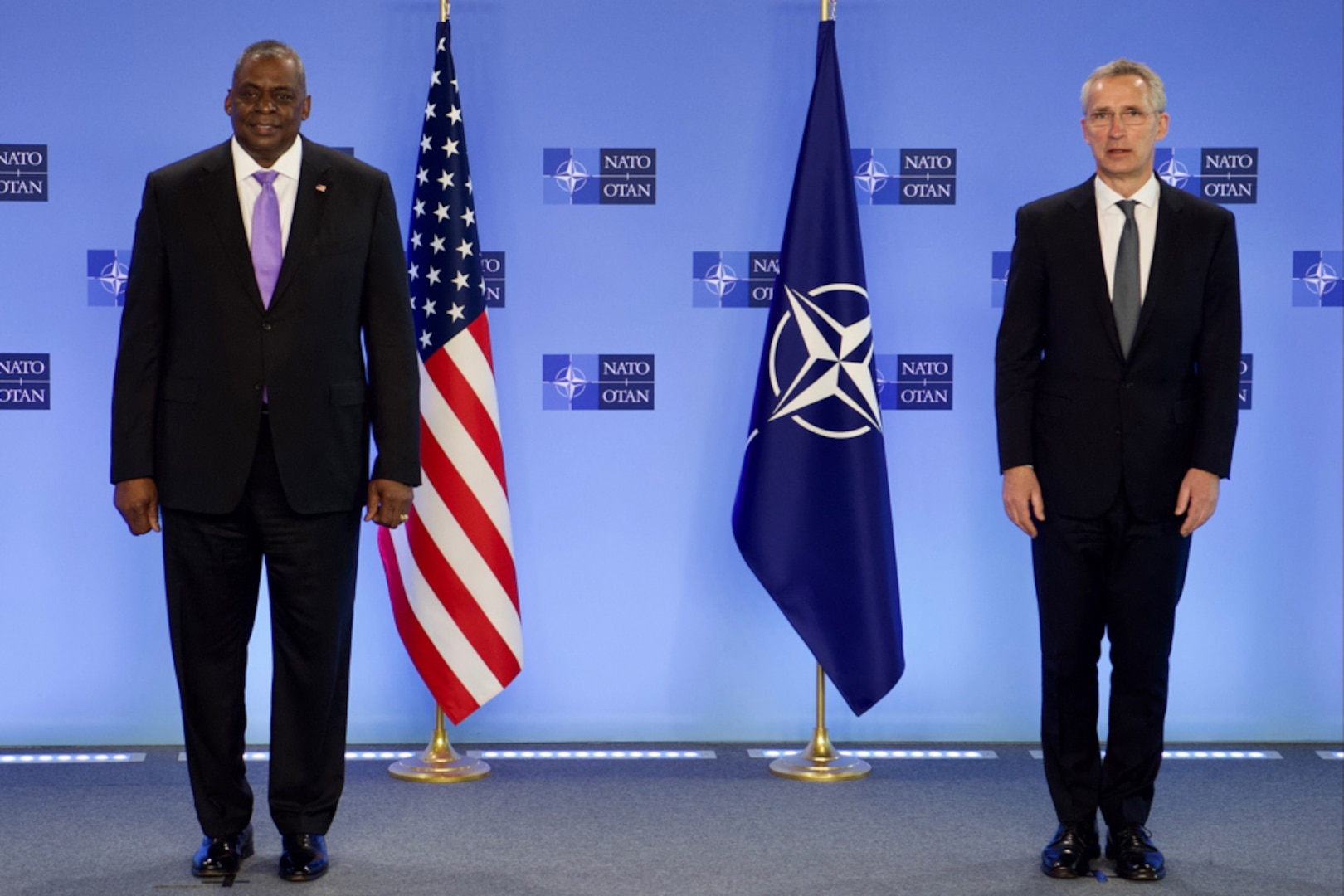 Two men stand beside each other next to U.S. and NATO flags.