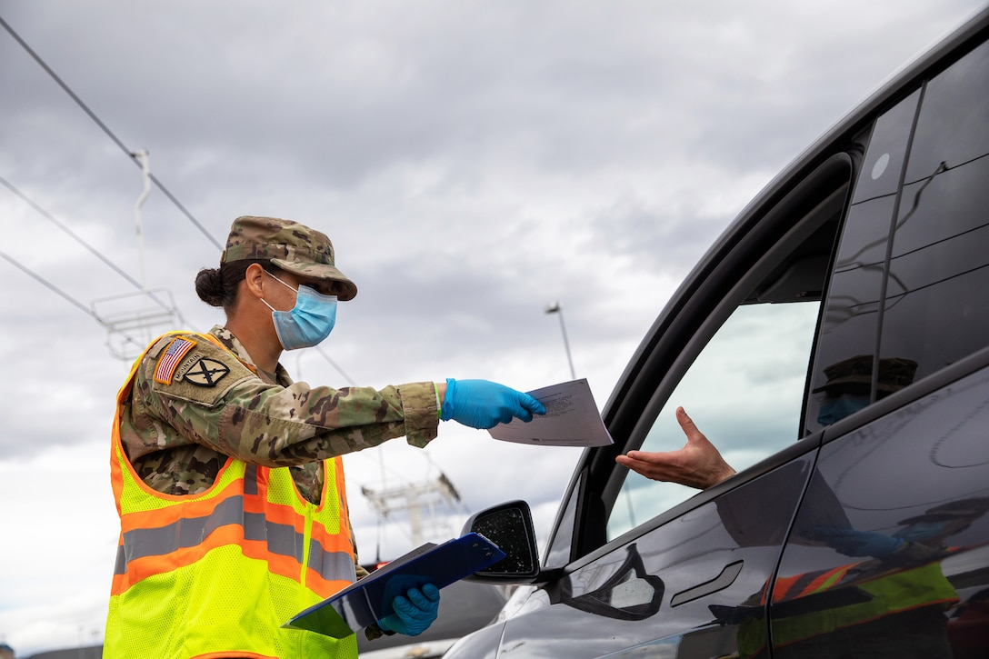 A soldier wearing a face mask and gloves hands a flyer to someone in a vehicle.
