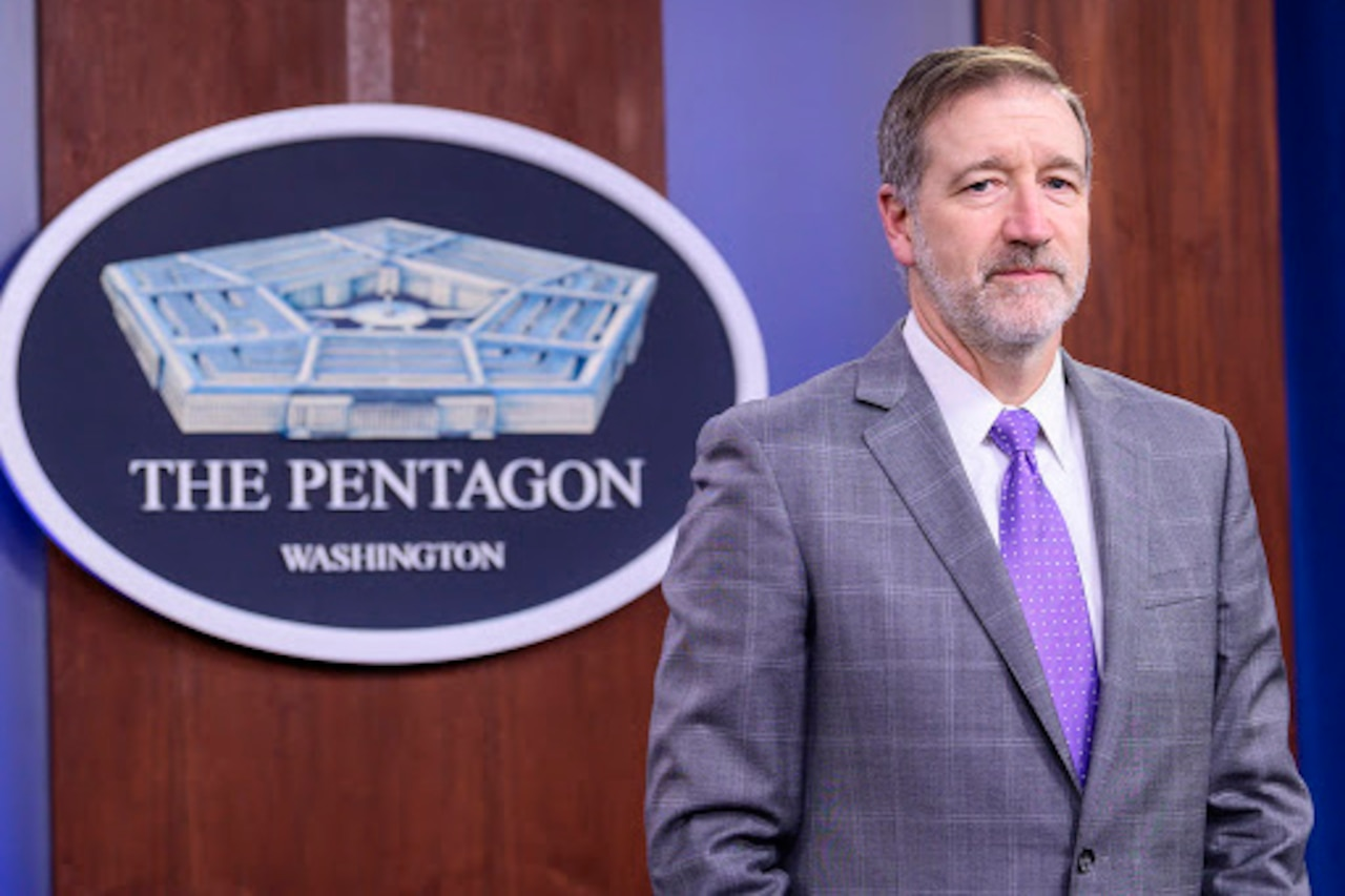 A man stands in front of a sign indicating that he is at the Pentagon.
