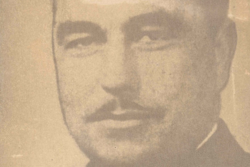 A man with a mustache smiles at the camera.