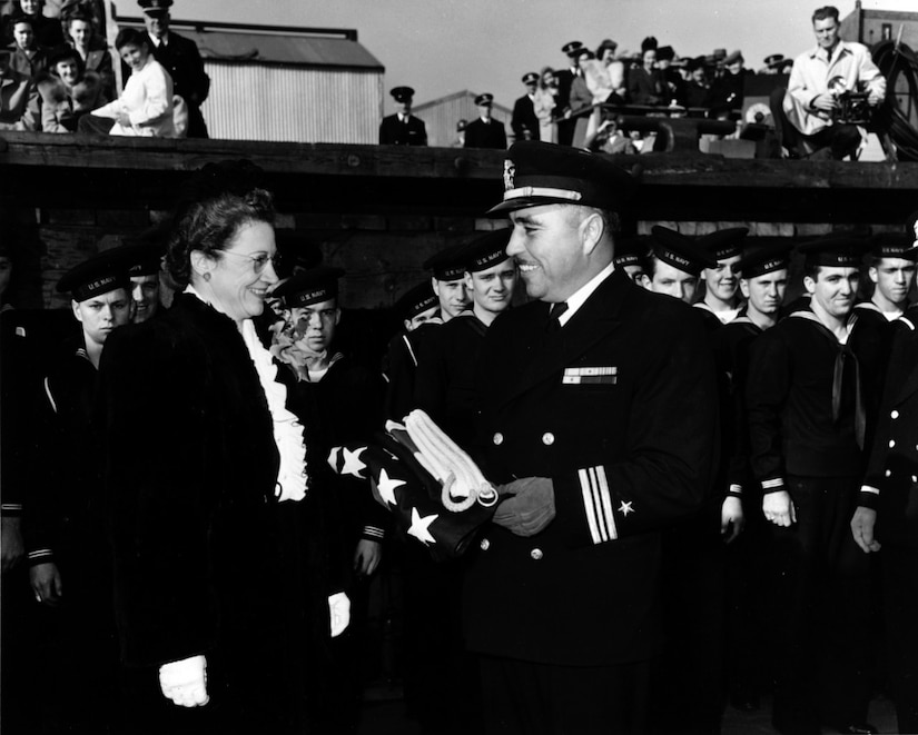 A man in a Navy officer's uniform, holding a folded U.S. flag, smiles at a woman. Sailors stand behind him.