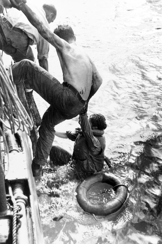 Two men hang onto the side of a ship as they work to pull a third man from the ocean.