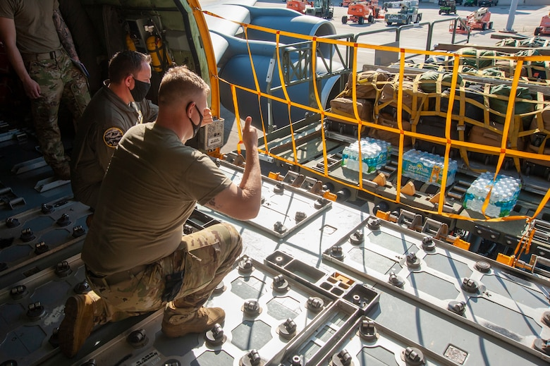 U.S. Air Force Airman 1st Class Tristan Shannon, a 91st Air Refueling Squadron (ARS) boom operator, signals to the K-Loader driver when pulling up to a KC-135 Stratotanker on the flightline, April 9, 2021, at MacDill Air Force Base, Fla. The K-Loader loaded bags belonging to Airmen from the 91st ARS that deployed to Al Udeid Air Base, Qatar. (U.S. Air Force photo by Airman 1st Class David D. McLoney)