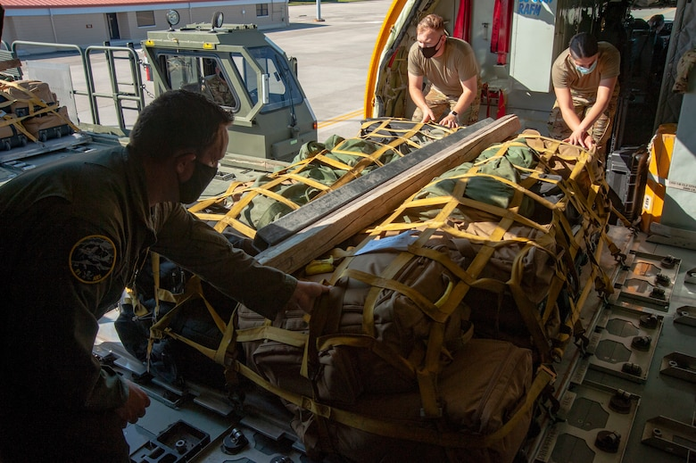 Airmen from the 91st Air Refueling Squadron roll cargo for a deployment onto a KC-135 Stratotanker aircraft, April 9, 2021, at MacDill Air Force Base, Fla. The cargo is loading and then secured on rollers, making it easy to offload when arriving at Al Udeid Air Base, Qatar. (U.S. Air Force photo by Airman 1st Class David D. McLoney)
