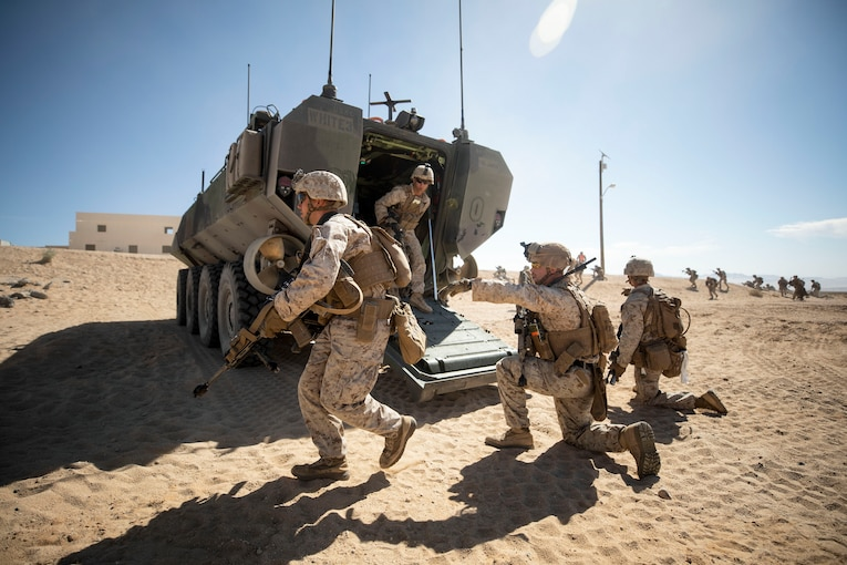 Marines run on sand near a parked amphibious vehicle.
