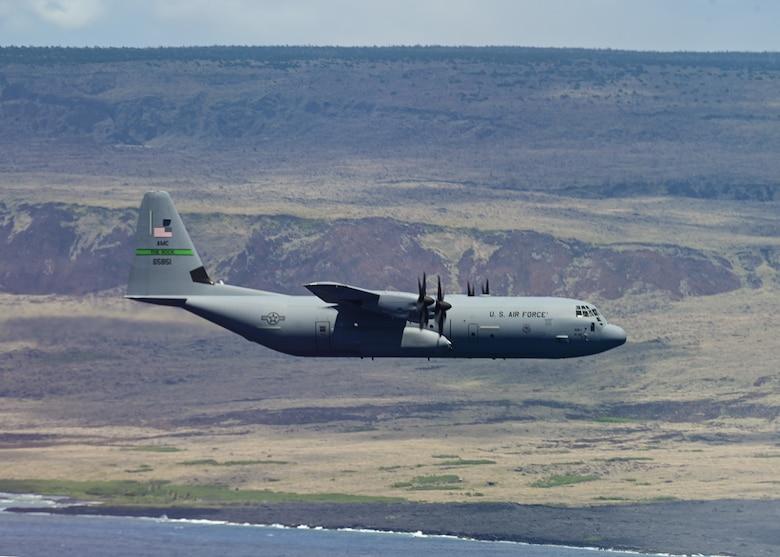An aircraft flies over the ocean in Hawaii