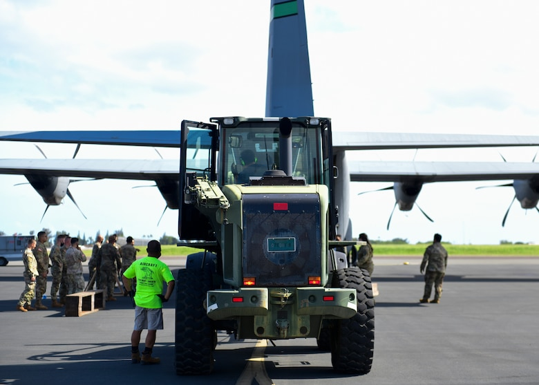 A forklift carries a M119 howitzer onto an aircraft