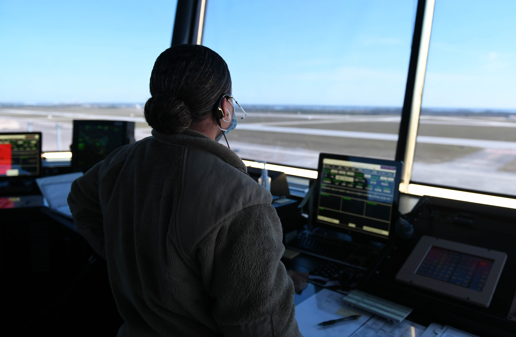 An Airman looks at the flightline from the air traffic control tower.