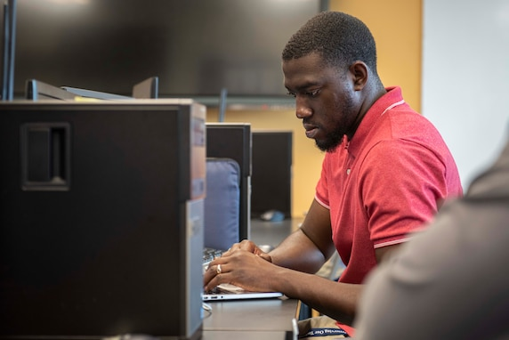 David Osafo, NSWC PCD engineer examines a virtual machine for possible vulnerabilities during the virtual 2021 HACKtheMACHINE challenge at Gulf Coast State College.