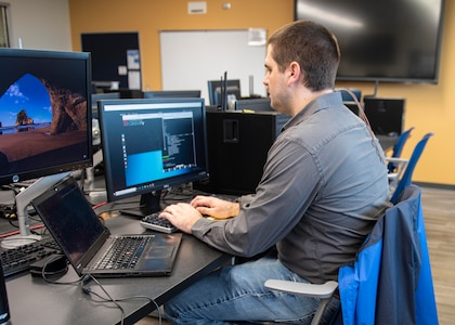 Joshua Davis, NSWC PCD engineer, develops python scripts to decode messages during the virtual 2021 HACKtheMACHINE challenge at Gulf Coast State College.