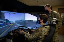 Woman sits in driving simulator while man looks over her shoulder.