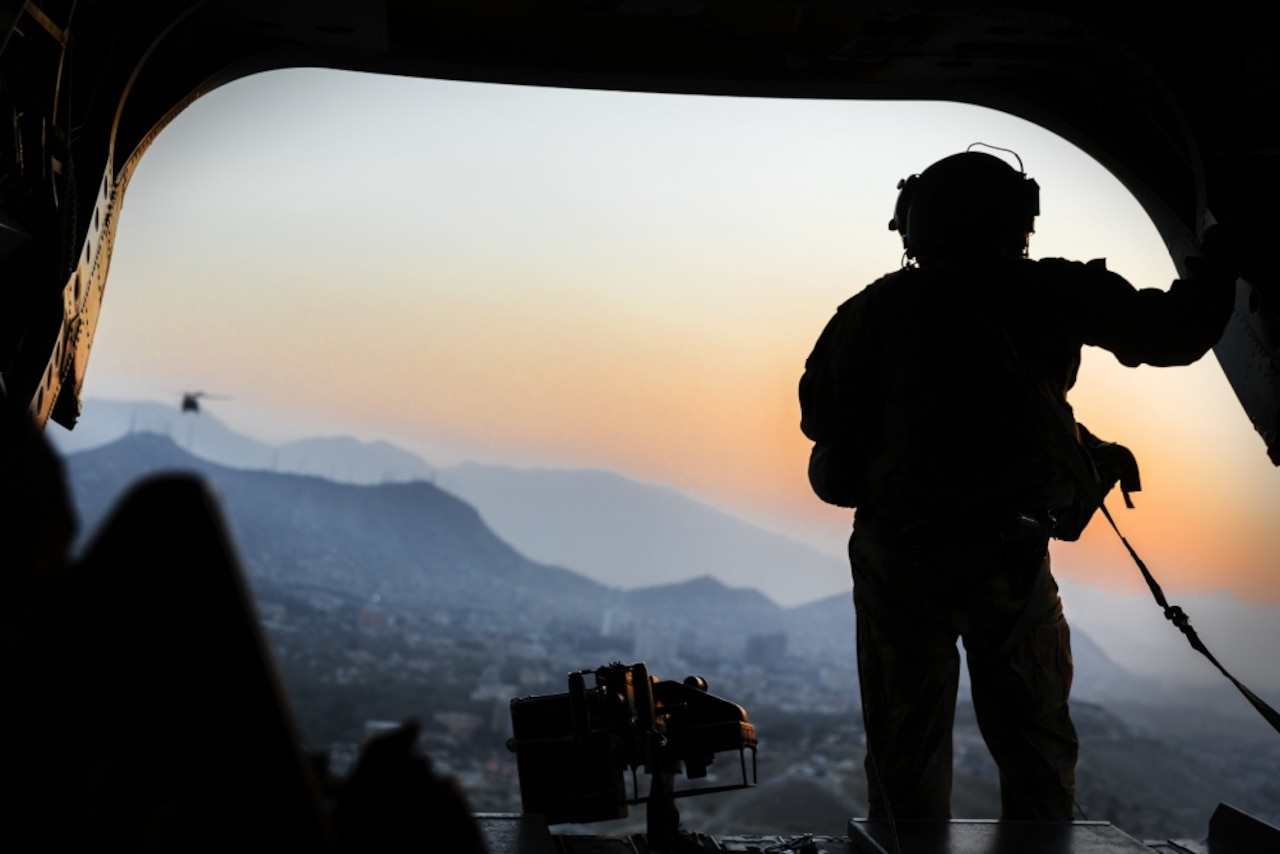 A soldier stands on the rear ramp of a helicopter.