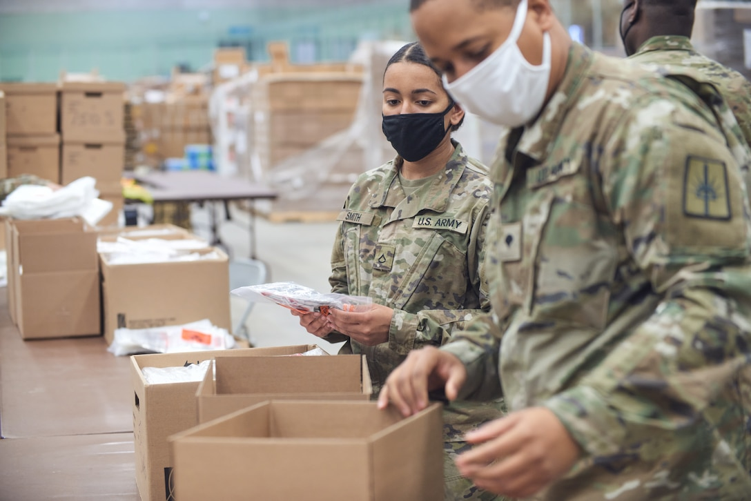 Army Pfc. Sydney Smith, with the 206th Military Police Company, and Spc. Claude Hamilton, a construction engineer assigned to the 1156th Engineer Company, assemble COVID-19 test kits to be shipped across New York state, at Hudson Valley Community College in Troy April 13, 2021. The Guard has helped assemble and ship 10 million test kits since last April.