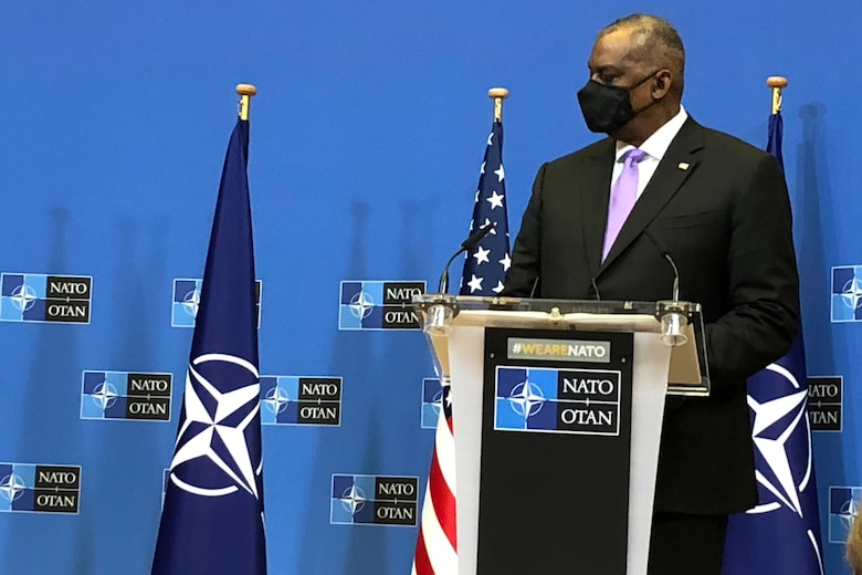 A man in business attire stands at a lectern with microphones and U.S. and NATO flags behind him.