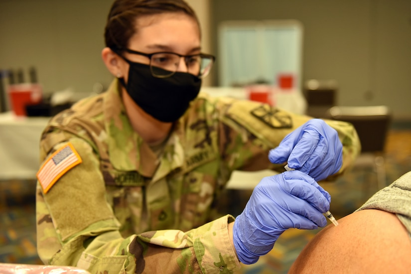 Michigan National Guard Soldiers with Michigan's Task Force Red Lion COVID-19 Vaccination/Testing Team help the Detroit Health Department vaccinate residents during a vaccination clinic at TCF Center, Detroit, Michigan, April 6, 2021.