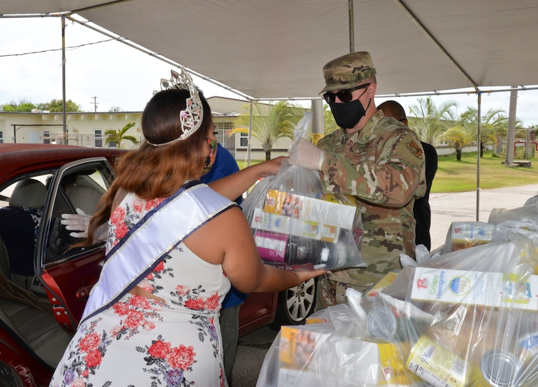 U.S. Air Force Staff Sgt. Nicholas Killian, 36th Civil Engineering Squadron workforce manager, hands a bag of food commodities to Kylani Ogo, Miss Voluptuous Pacific and Yona resident, during a COVID-19 relief food distribution event at the community gym in Yona, Guam, April 15, 2021. The 36th CES is Yona's sister squadron, as part of the Andersen Air Force Base Sister Village Sister Squadron program, through which squadron members collaborate with Guam residents in activities to strengthen their friendship and partnership. (U.S. Air Force photo by Alana Chargualaf)
