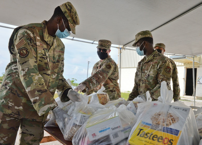 U.S. Air Force Airmen assigned to the 36th Civil Engineering Squadron place food commodities onto a table during a COVID-19 relief food distribution event at the community gym in Yona, Guam, April 15, 2021. The 36th CES is Yona's sister squadron, as part of the Andersen Air Force Base Sister Village Sister Squadron program, through which squadron members collaborate with Guam residents in activities to strengthen their friendship and partnership. (U.S. Air Force photo by Alana Chargualaf)