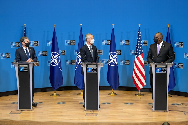 Three men stand on a stage.