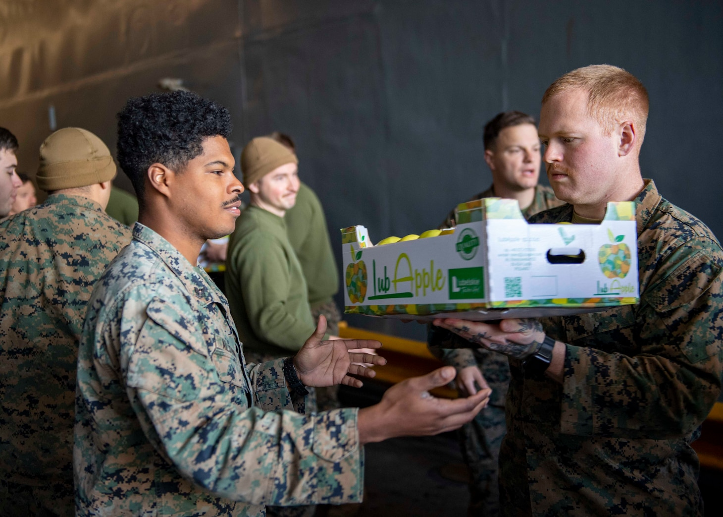 Hospital Corpsman 3rd Class Jameel Alston, left, and Hospital Corpsman Seaman Logan Vincent, both assigned to the 24th Marine Expeditionary (24th MEU), move supplies aboard the Harpers Ferry-class dock landing ship USS Carter Hall (LSD 50) during a replenishment-at-sea, April 12, 2021.