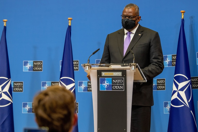 Secretary of Defense Lloyd J. Austin III listens to a question while standing behind a dias.