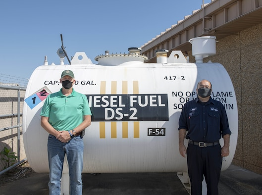 Photo of two people in front of fuel tank.