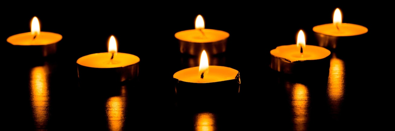 a close up image of Votif candles casting light in a dark area
