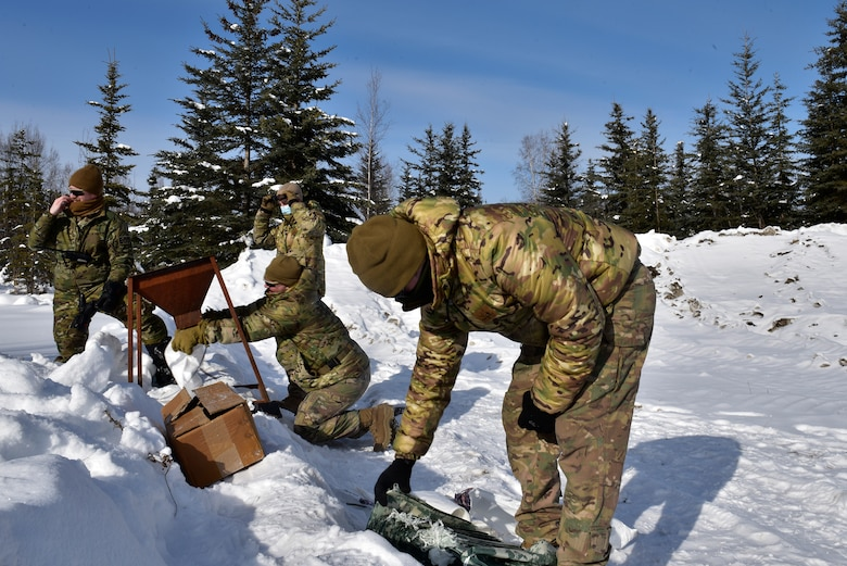 U.S. Air Force Airmen from the 354th Civil Engineer Squadron Explosive Ordnance Disposal (EOD) Flight prepare bags for the snow mitigation experiment on March 18, 2021, at Eielson Air Force Base, Alaska. The experiment tested the use of snow to help mitigate explosive effects. Because of Alaska's arctic environment, the usual method of using water to reduce blast wave peak pressures is often impractical. Therefore, Icemen Spark and EOD sought to use a more readily available material: snow. (U.S. Air Force photo/Senior Airman Danielle Sukhlall)
