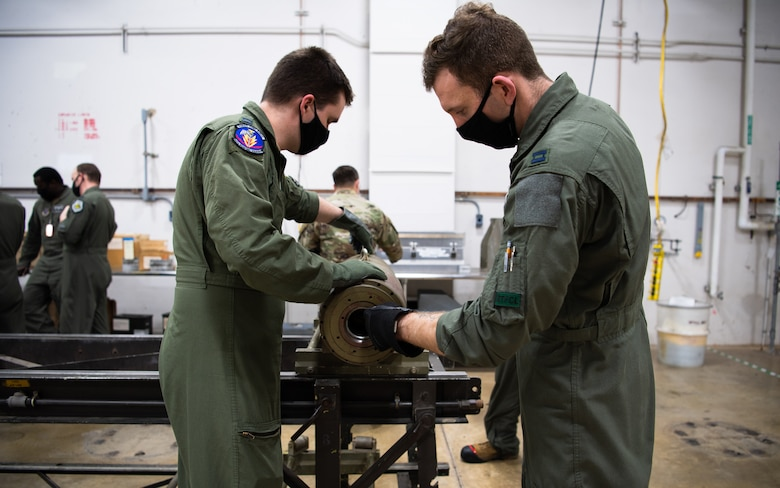 Capts. Samuel Shrewsberry and Michael McBrien, 340th Weapons Squadron weapons instructor course students, inspect training munitions during a training bomb build at Barksdale Air Force Base, Louisiana, April 13, 2021. The Airmen from the 340th WPS trained with the 2nd Munitions Squadron to better learn and understand what it takes to build munitions. (U.S. Air Force photo by Airman 1st Class Jacob B. Wrightsman)