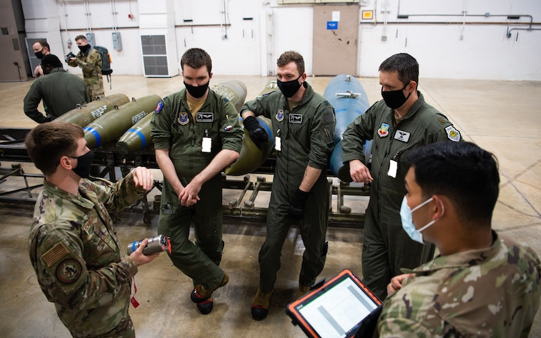 Airmen from the 340th Weapons Squadron receives instruction from Senior Airman Chad McCannon, bottom left, 548th Combat Training Squadron munitions liasion, during a training bomb build at Barksdale Air Force Base, Louisiana, April 13, 2021. Airmen from the 340th WPS integrated with the 2nd Munitions Squadron to teach the students the components and procedures that go into assembling a bomb. (U.S. Air Force photo by Airman 1st Class Jacob B. Wrightsman)