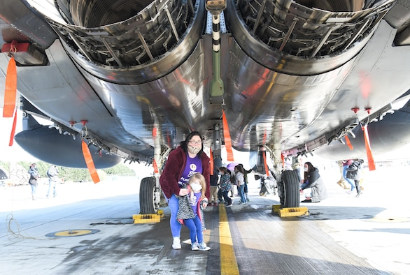 A 48th Fighter Wing civilian shows a child around an F-15E Strike Eagle during a tour supporting the Month of the Military Child on April 15, 2021, at Royal Air force Lakenheath, England. Approximately 2 million military children have experienced a parental deployment since 9/11. (U.S. Air Force photo by Senior Airman Shanice Ship)
