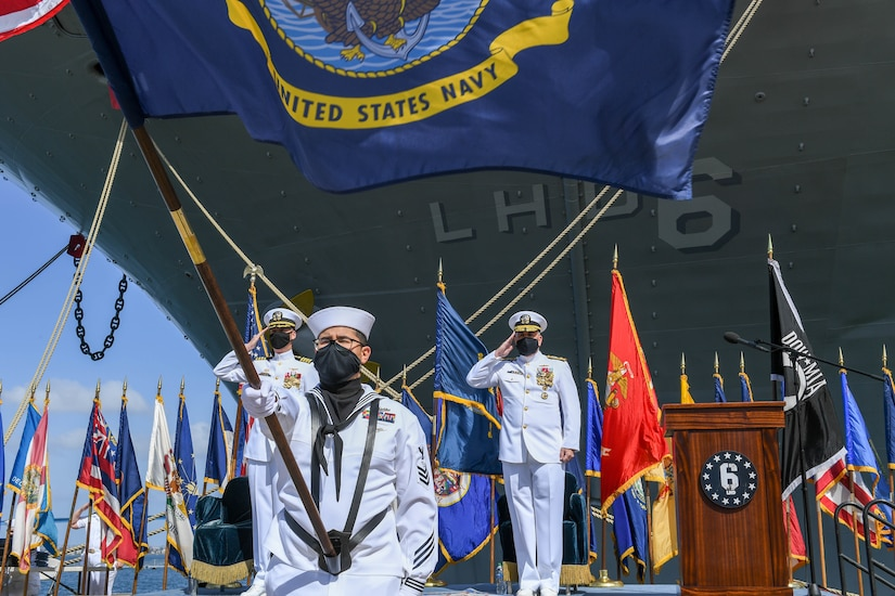 Navy officers salute a flag during a ceremony.