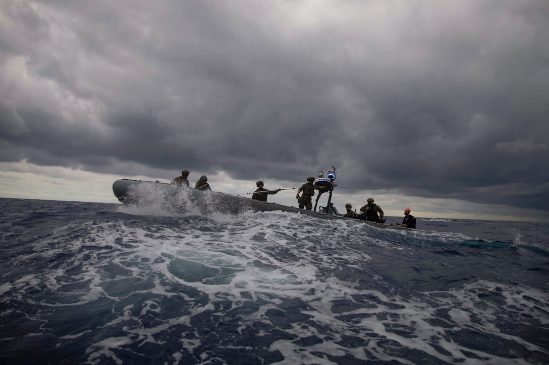 Coast Guardsmen and sailors ride in an inflatable boat in rough waters.