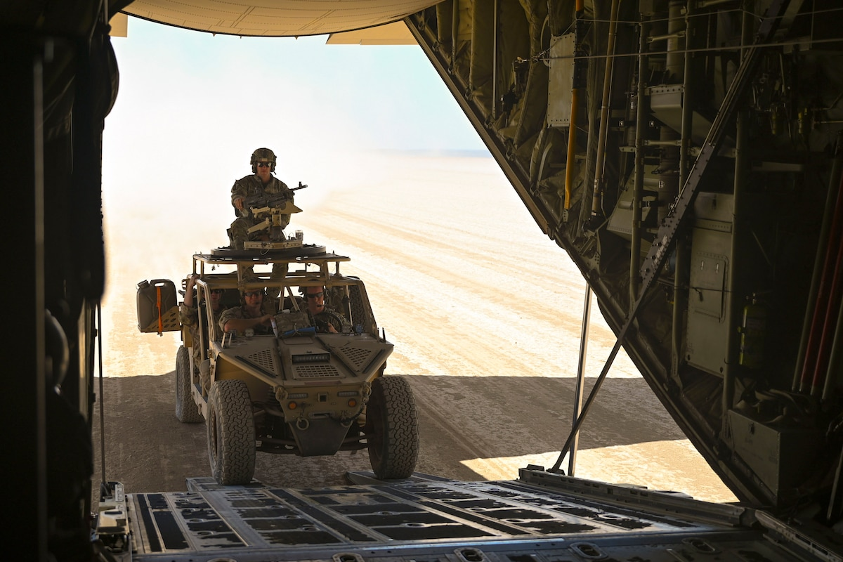 Airmen drive a tactical vehicle into an aircraft parked in a desert.
