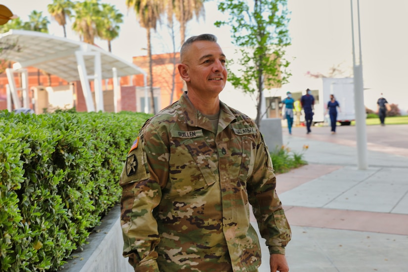 A soldier smiles as he stands on a wide sidewalk.