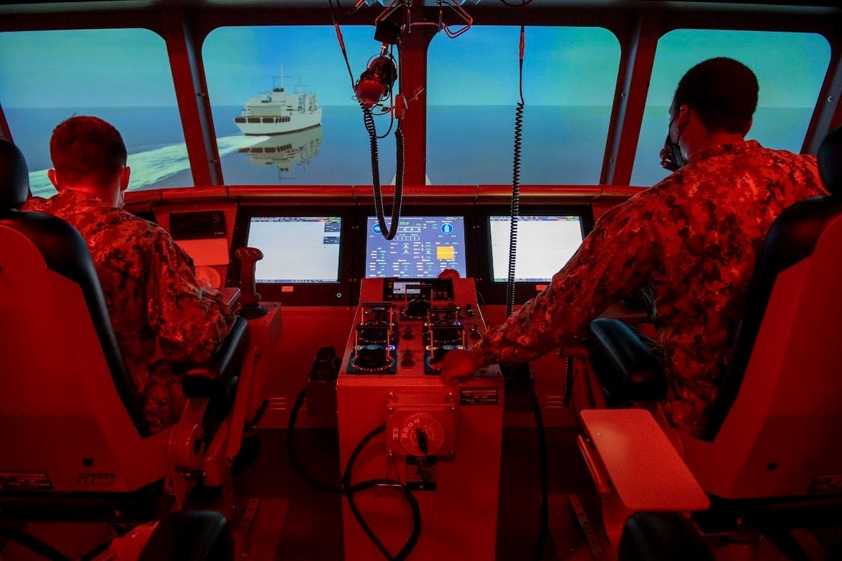 Two sailors illuminated by red light sit inside a simulated ship.