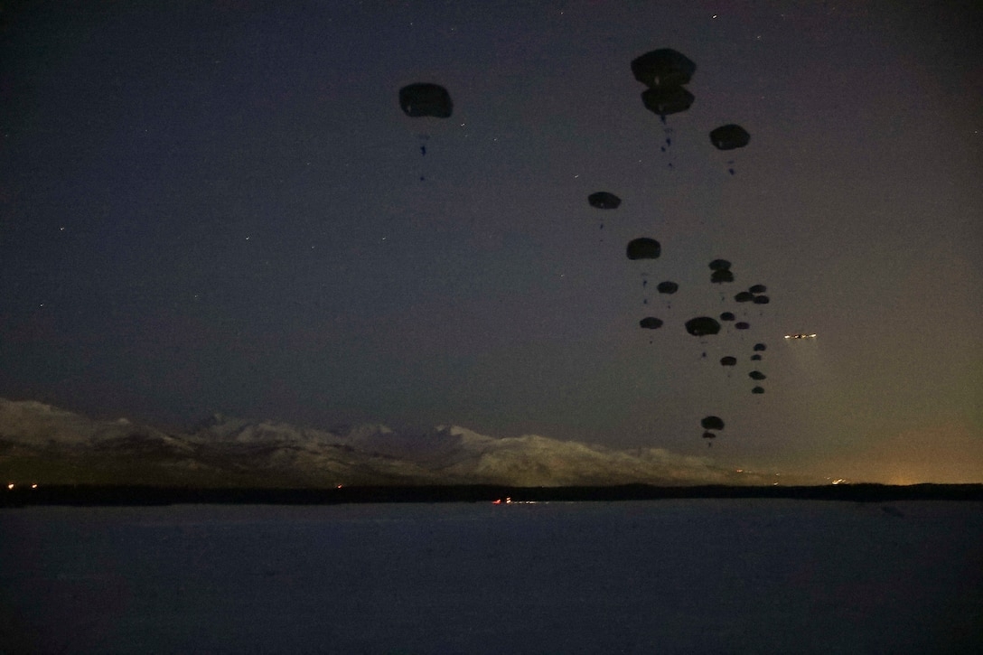 Soldiers freefall with parachutes at night.