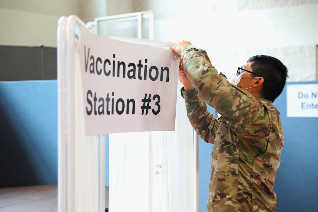 A soldier wearing a face mask takes down a vaccine sign.