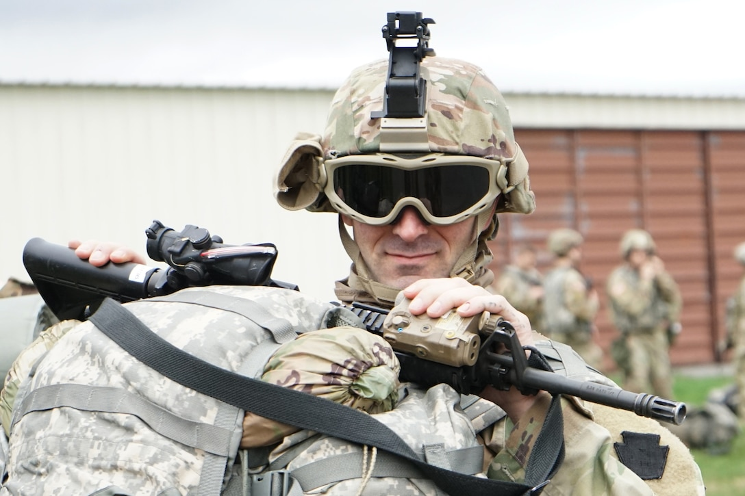 A soldier wearing goggles smiles at the camera as he holds a gun and baggage.